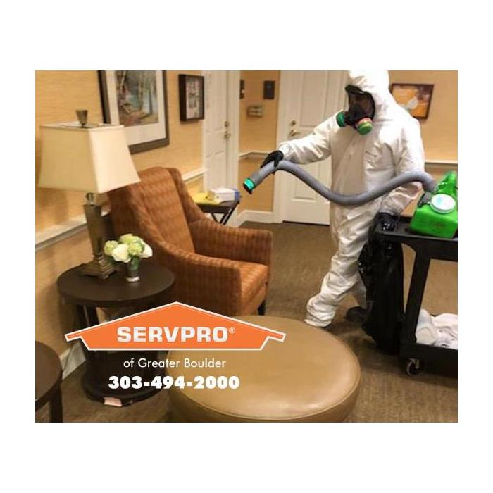 SERVPRO technician dressed in PPE cleaning a sitting room in a senior citizens home with cleaning equipment..