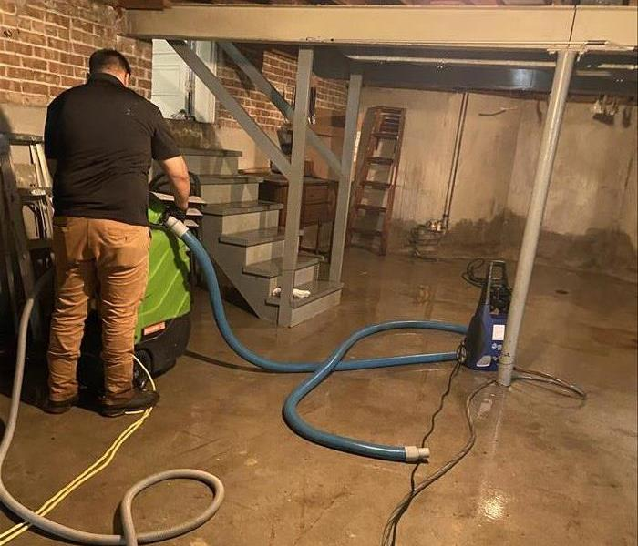 SERVPRO tech cleaning out flooded basement in Louisville
