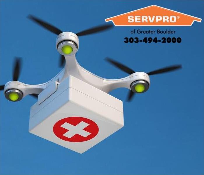 Flying drone transporting an emergency kit.