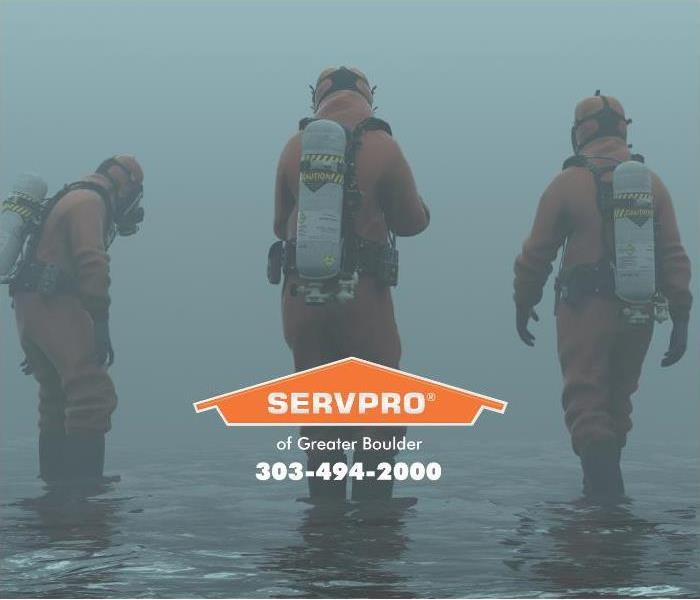 An image of technicians in wet suits assessing water damage in a flooded area.