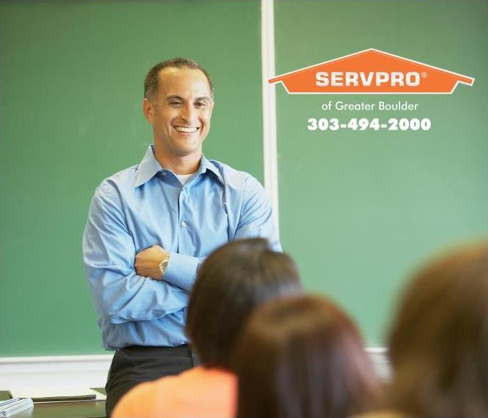 A continuing education instructor smiles at a classroom of adult students.